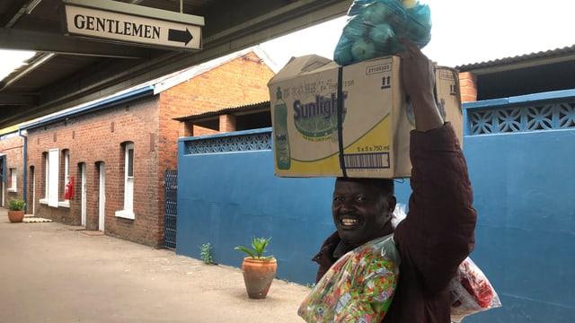 Ein Mann beladen mit Kartonschachteln und Taschen im Bahnhof von Bulawayo.