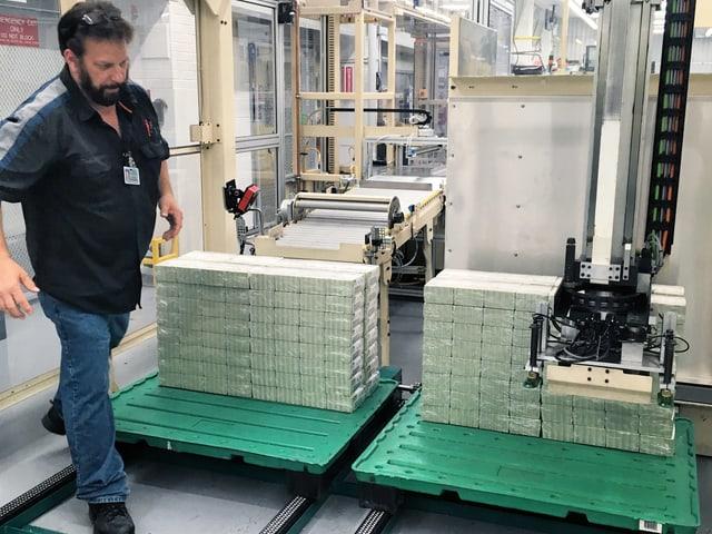 Im Bureau of Engraving and Printing: ein Mitarbeiter läuft an Geldstapeln vorbei.