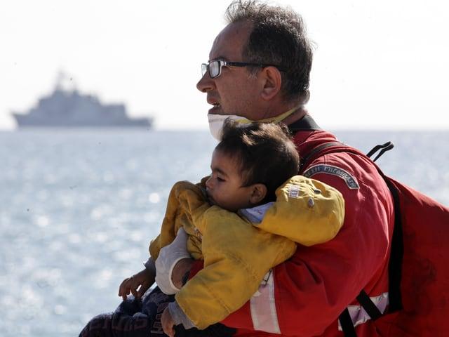 Retter mit Kind im Arm vor offenem Meer
