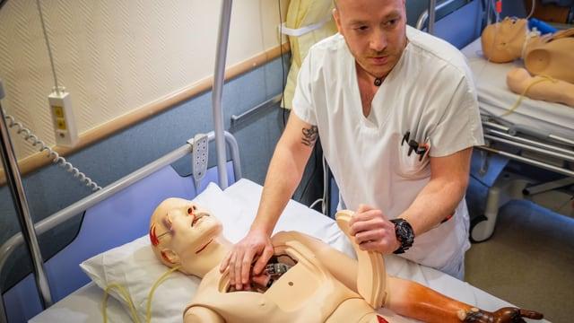 Mann hantiert mit Medizinpuppe