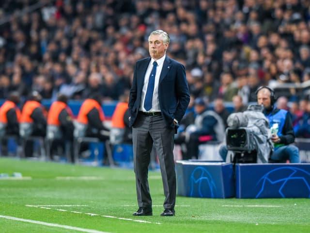 Carlo Ancelotti steht mit beiden Händen in den Hosentaschen vor der Fankurve.