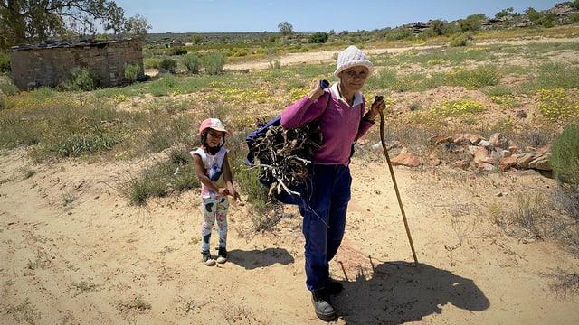 Eine Bäuerin der Khoi San und ihre kleine Tochter am Holz sammeln in Südafrika.