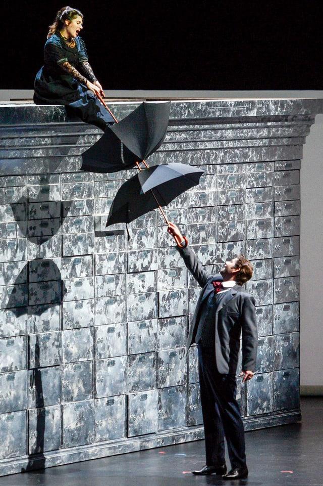 Kathryn Lewek und David Stout mit Regenschirm im Stück «The Merchant of Venice» auf der Bühne.