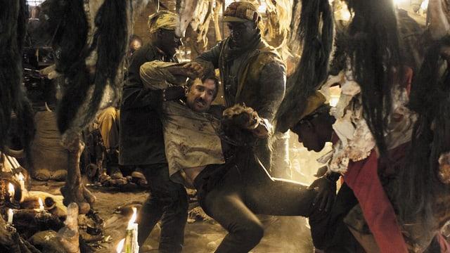 Ein Mann wird von drei Männern in einem ärmlichen Wohnviertel gepackt.
