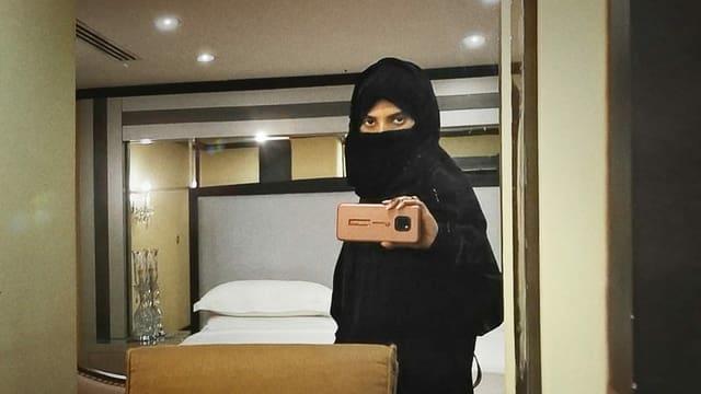 Eine Araberin fotografiert ihr Spiegelbild mit dem Smartphone.