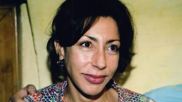 Frau mit schwarzen Haaren vor gelbem Hintergrund