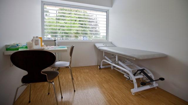 Ein weisser Raum mit Holzboden und einem Fenster, in der Ecke ein Behandlungstisch.
