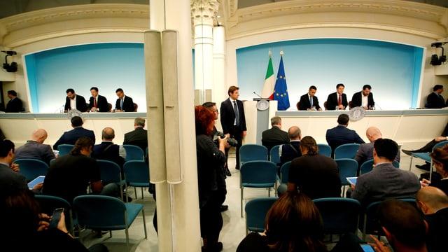 Drei Männer in Anzügen an einer Pressekonferenz