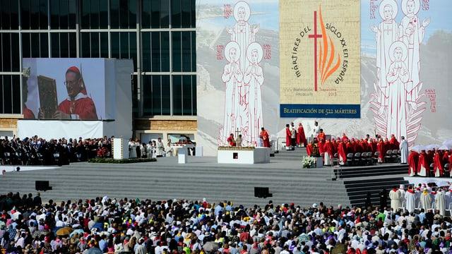Hunderte Zuschauer vor einer Bühne, auf der Geistliche stehen