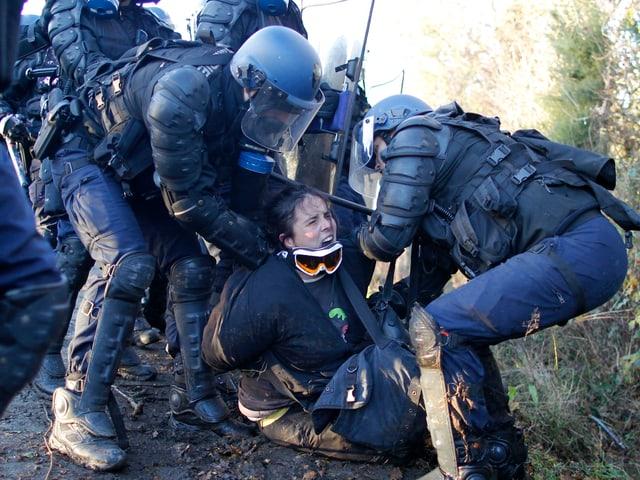 Polizisten in Kampfmontur drücken eine schreiende Frau mit heruntergerissener Skibrille auf den Boden.
