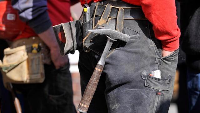 Hüfte eines Bauarbeiters mit einem umgebundenen Werkzeuggürtel, daran baumelt ein Hammer.