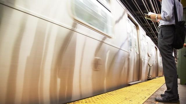 Ein Mann steht lesend am Bahnsteig, wo gerade eine U-Bahn einfährt.
