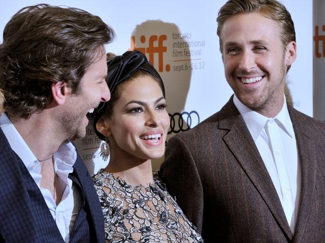 Bradley Cooper, Eva Mendes unr Ryan Gossling an einer Veranstaltung.