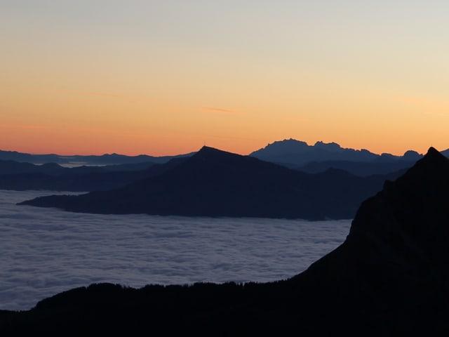 Die Berge sind noch im Dunkeln. Im Tal liegt das helle Nebelmeer. Darüber ein Himmel in zartrötlicher Dämmerungsfarbe.