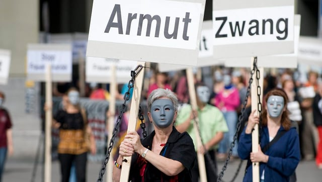 Frauen mit Masken im Gesicht tragen Plakate durch die Strasse. Auf denen steht: «Armut» und «Zwang».