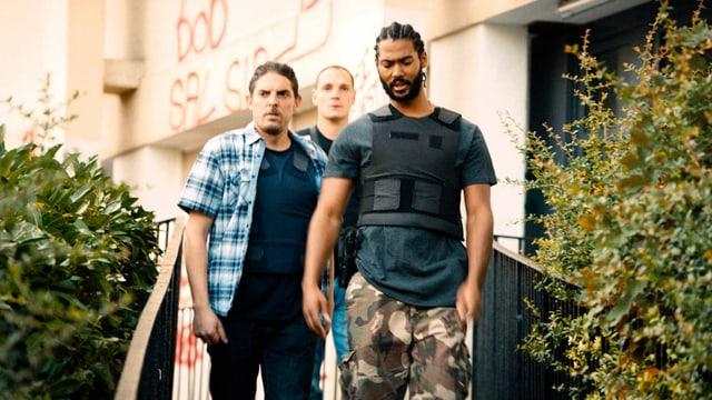 Drei Polizisten in Strassenkleidung.