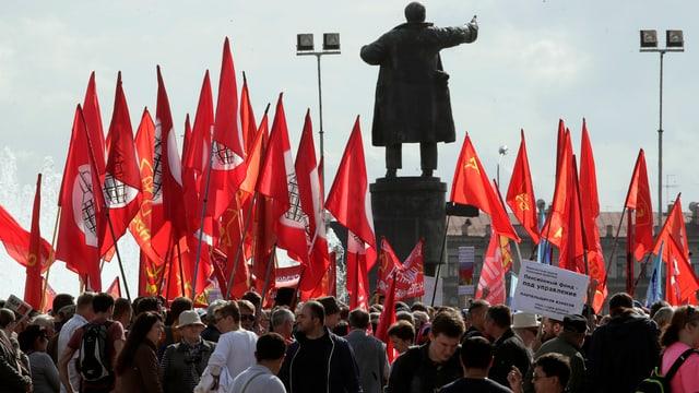 Demonstranten und rote Fahnen um eine Lenin-Statue.