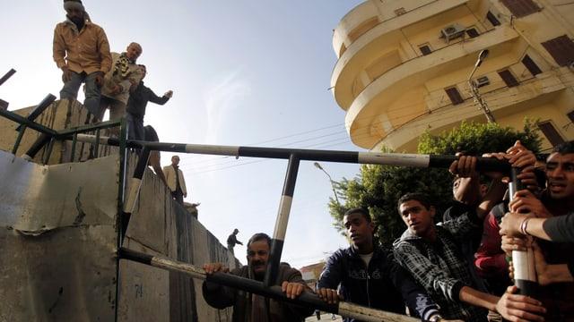 Demonstranten wollen eine Strassensperrung aufbrechen, die den Weg zum Präsidentenpalast blockiert. (reuters)