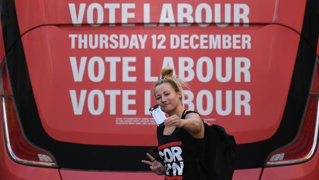 Eine Frau macht ein Selfie vor einer Labour-Werbung