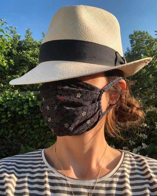 Eine Frau mit Hut und Mundschutz mit Blümchenmuster