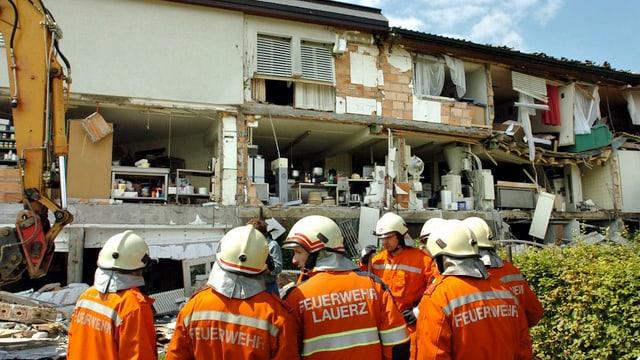 Haus nach einer Explosion, im Vordergrund Feuerwehrleute
