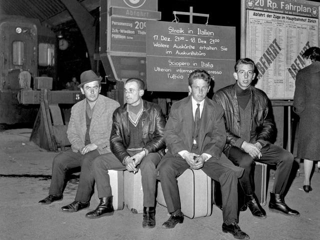 Männer auf ihren Koffern sitzend auf dem Perron