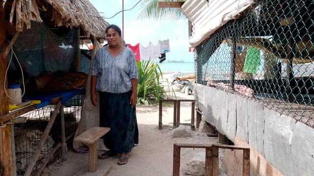 Eine Frau steht neben einer Hütte.