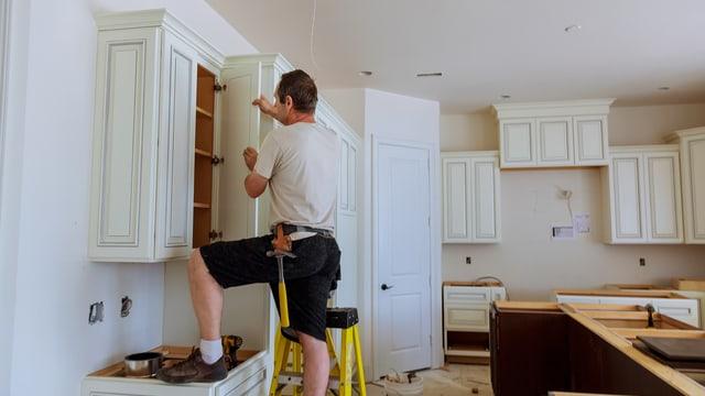 Ein Handwerker montiert eine neue Küche.