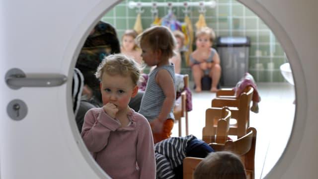 Symbolbild: Aufnahme durch das Fenster in einer Türe in eine Kinderkrippe hinein.