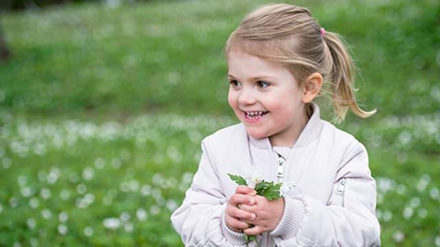 Die kleine Prinzessin Estelle lächelt mit einer Blume in der Hand.