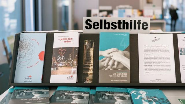 """Ein Tisch, auf dem Bücher und Broschüren ausliegen. Obendran ein Zettel mit der Überschrift: """"Selbsthilfe""""."""