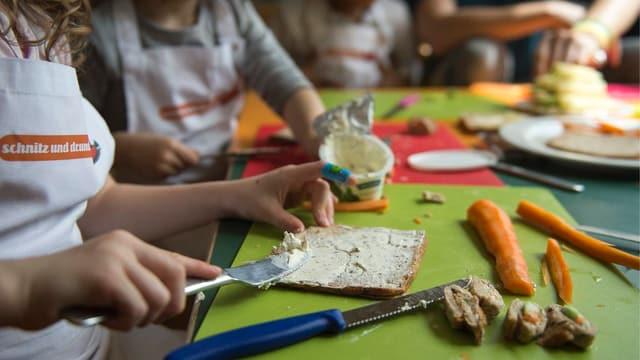 Kinder am Brötchen streichen.