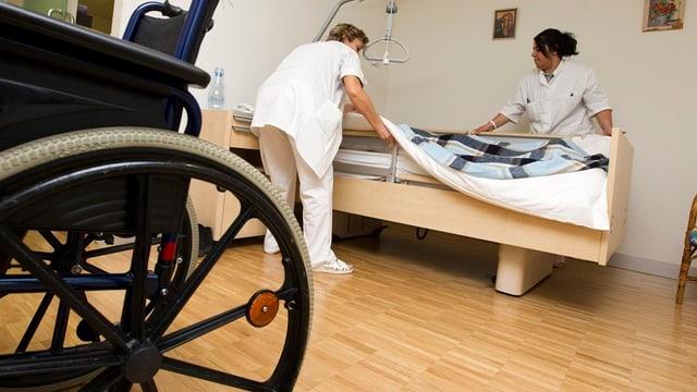 Pflegepersonal arbeitet in Patientenzimmer.