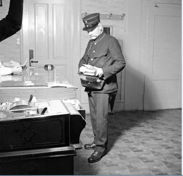 Ein Briefträger bringt einem Kunden die Post nachhause.
