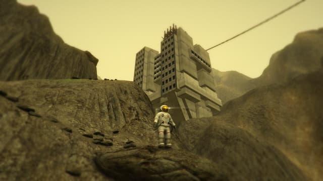 Der Astronaut steht vor einem Betongebäude im Gebirge.