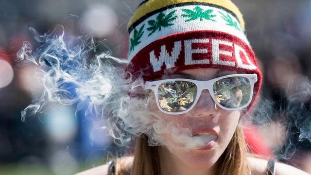 Eine Frau atmet Rauch aus.