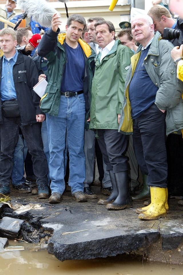 Schröder in Begleitung von Rettungskräften beim Hochwasser von 2002.