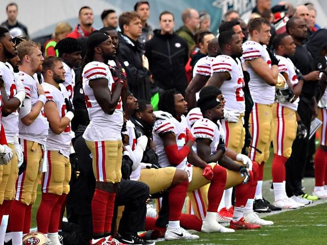 NFL-Profis knien während dem Abspielen der Hymne nieder