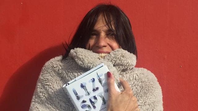 Annette König hat einen warmen Kunstfaserpelz an und hält das Buch «Und es schmilzt» von Lize Spit in der Hand.