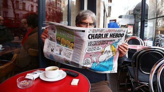 """Ein Mann in einem Café liest die Zeitung """"Charlie Hebdo""""."""
