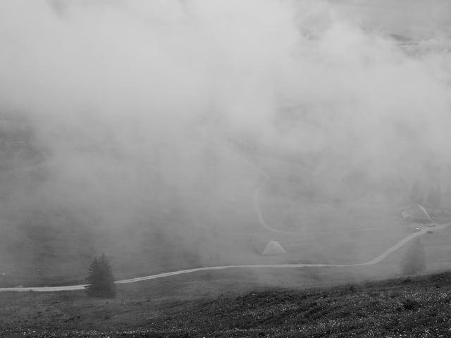 Schwarz-Weiss-Foto: Blick in ein Tal, in der Luft hängt Nebel.