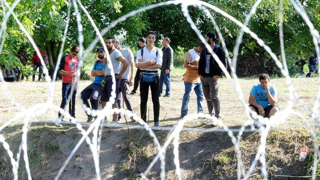 Hinter einem Stacheldrahtzaun stehen und sitzen Flüchtlinge.