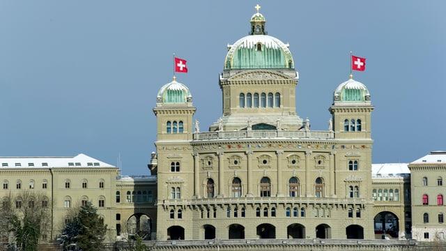 Das Bundeshaus mit wehenden Schweizer Fahnen und schneebedeckten Kuppeln.