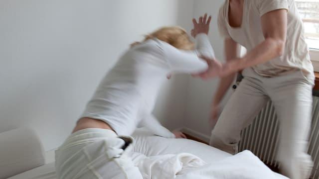 Ein Mann schlägt eine Frau. Gestellte Szene.