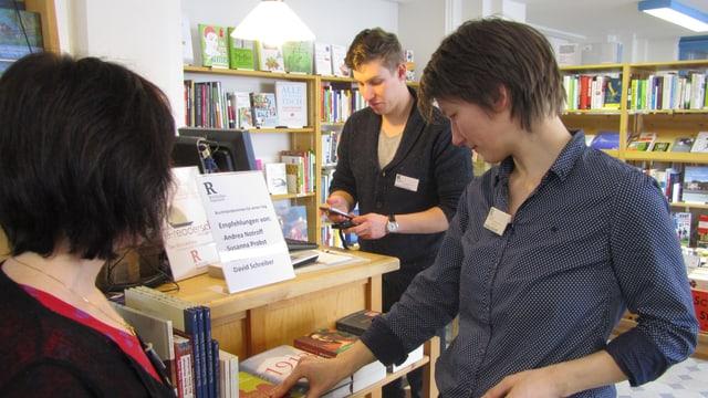 Drei der vier Buchhändlerinnen auf Zeit umringen das Regal mit ihren persönlichen Buchtipps.