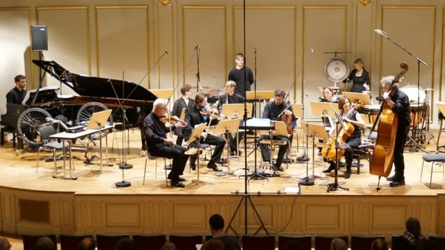 Ensemble auf einer Bühne, am linken Bühnenrand steht ein umgekehrtes Fahrrad.