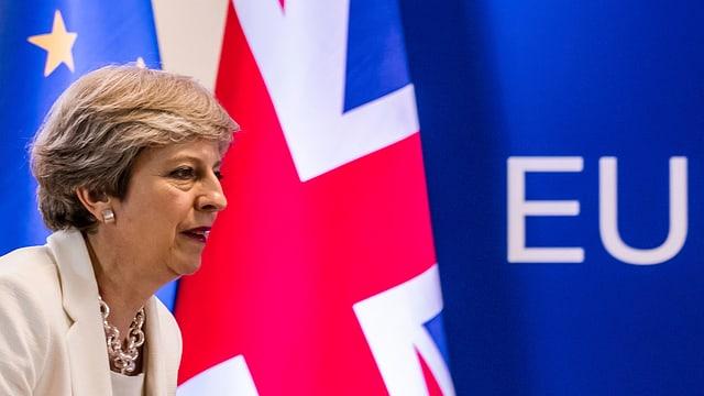 Theresa May avant las bandieras da la Gronda Britannia e da l'UE.