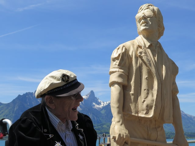 Polo Hofer neben seiner Statue, im Hintergrund der Thunersee