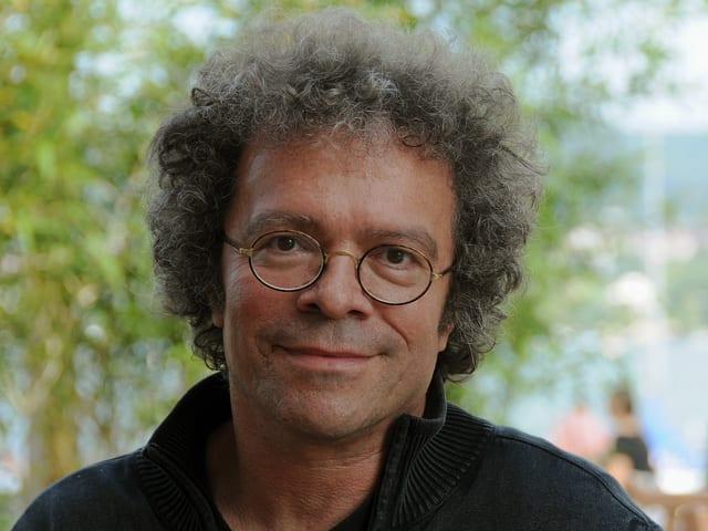 Der Regisseur Sandro Lunin schaut vor dem Hintergrund des Zürichsees in die Kamera.