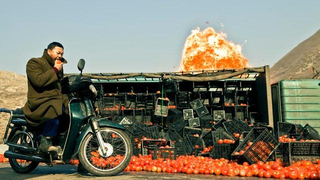 Ein Mann sitzt auf einem Motorrad, hinter ihm liegt ein umgekippter Laster, am Boden liegen Tomaten. Im Hintergrnd ist eine Explosion zu sehen.